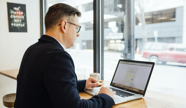 Man using his laptop in cafe as part of remote working following the global pandemic