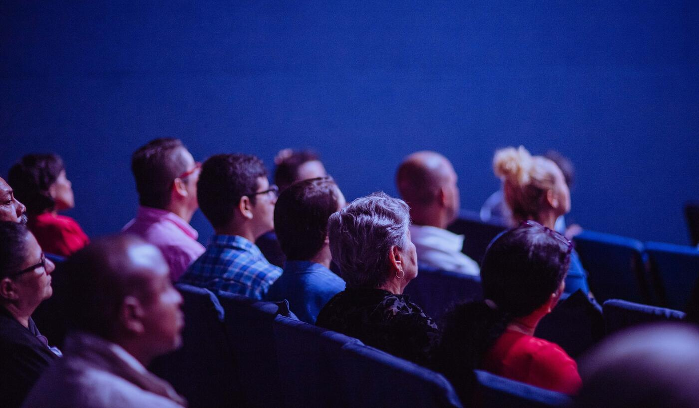 Crowd attend an industry conference and listen to a speaker presenting