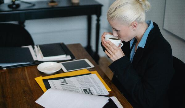 Woman in business attire sips coffee whilst reading legal documentation