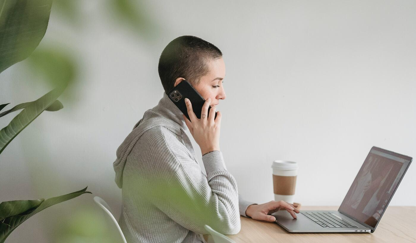 Woman with short hair takes a call whilst working from home as she works from her laptop