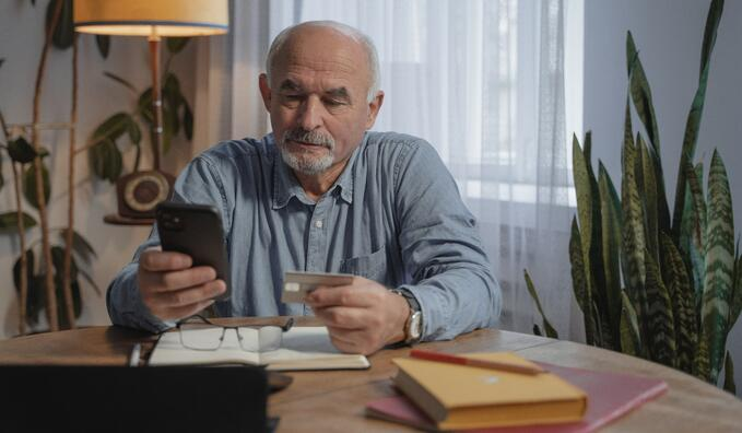 Older man wearing a blue shirt has his phone and credit card in hand
